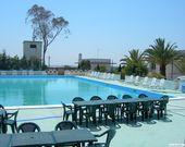 Schwimmbad mit Liegestühlen und Tischen